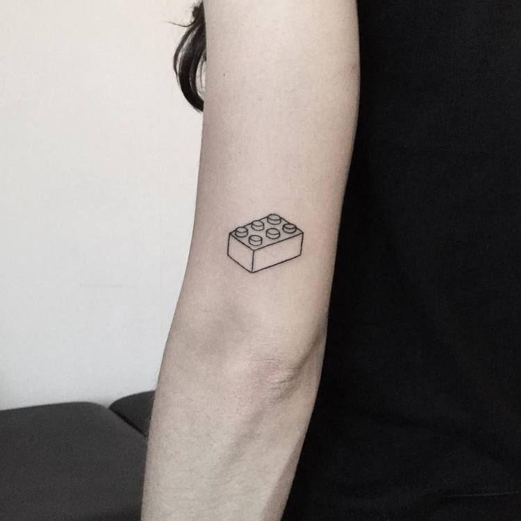 Lego brick tattoo on the left arm