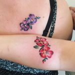 Matching flower tattoos on the back and arm