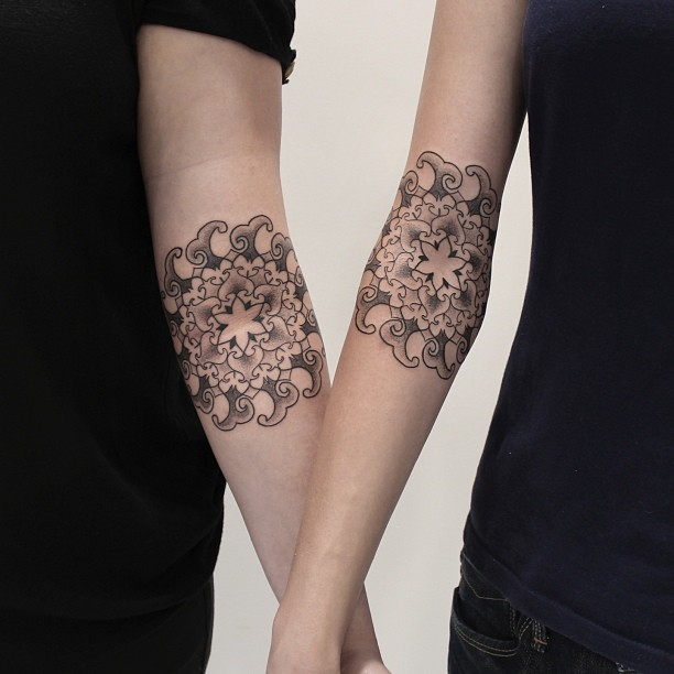 Matching mandala tattoos on arms