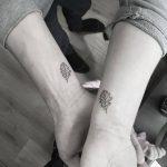 Matching minimal black leaves tattoos