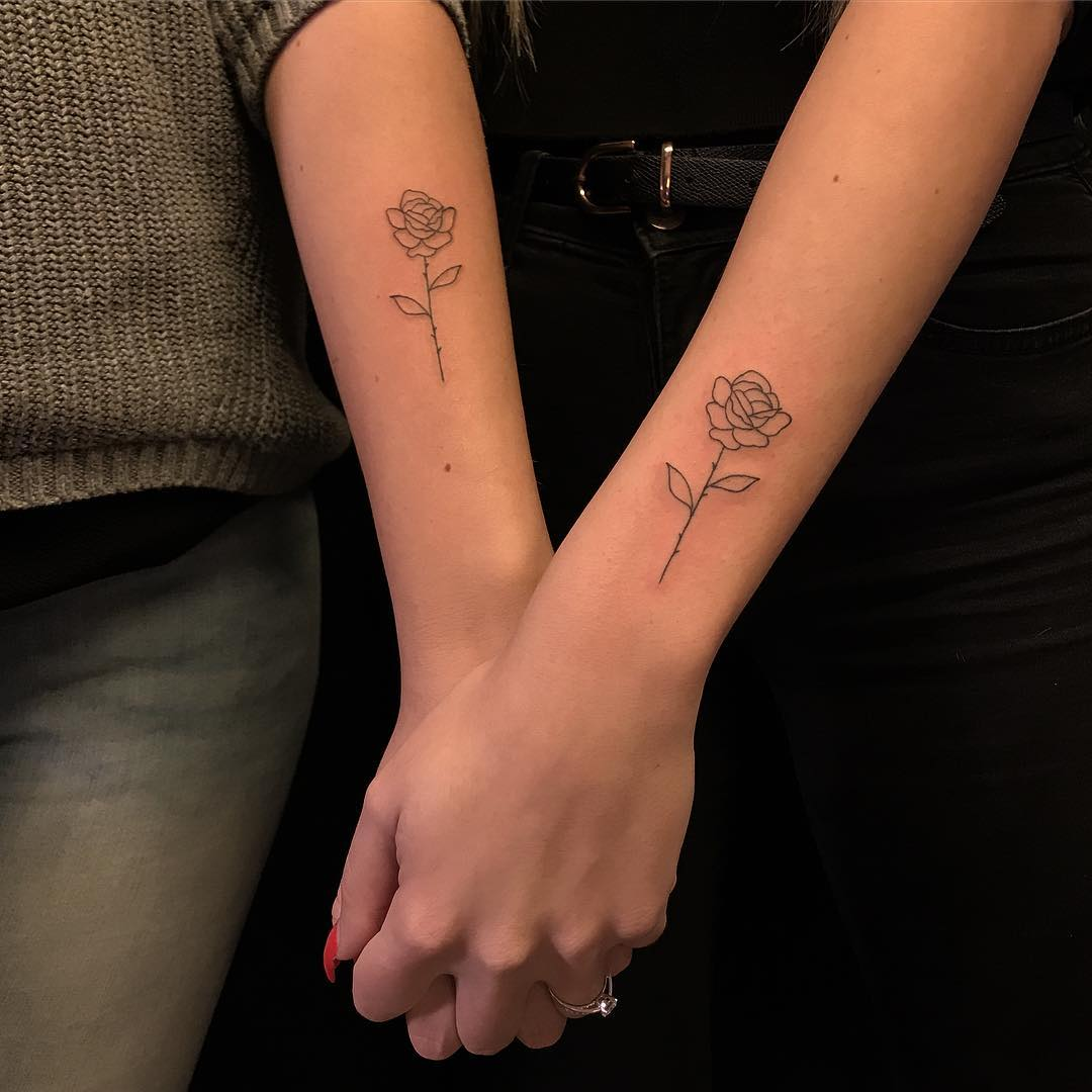 Matching rose tattoos on arms