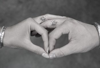 Matching saturn tattoos on fingers