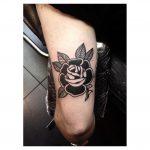Negative space black rose tattoo