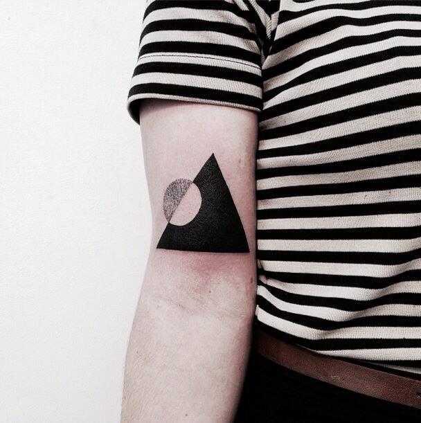 Negative space circle in a triangle tattoo