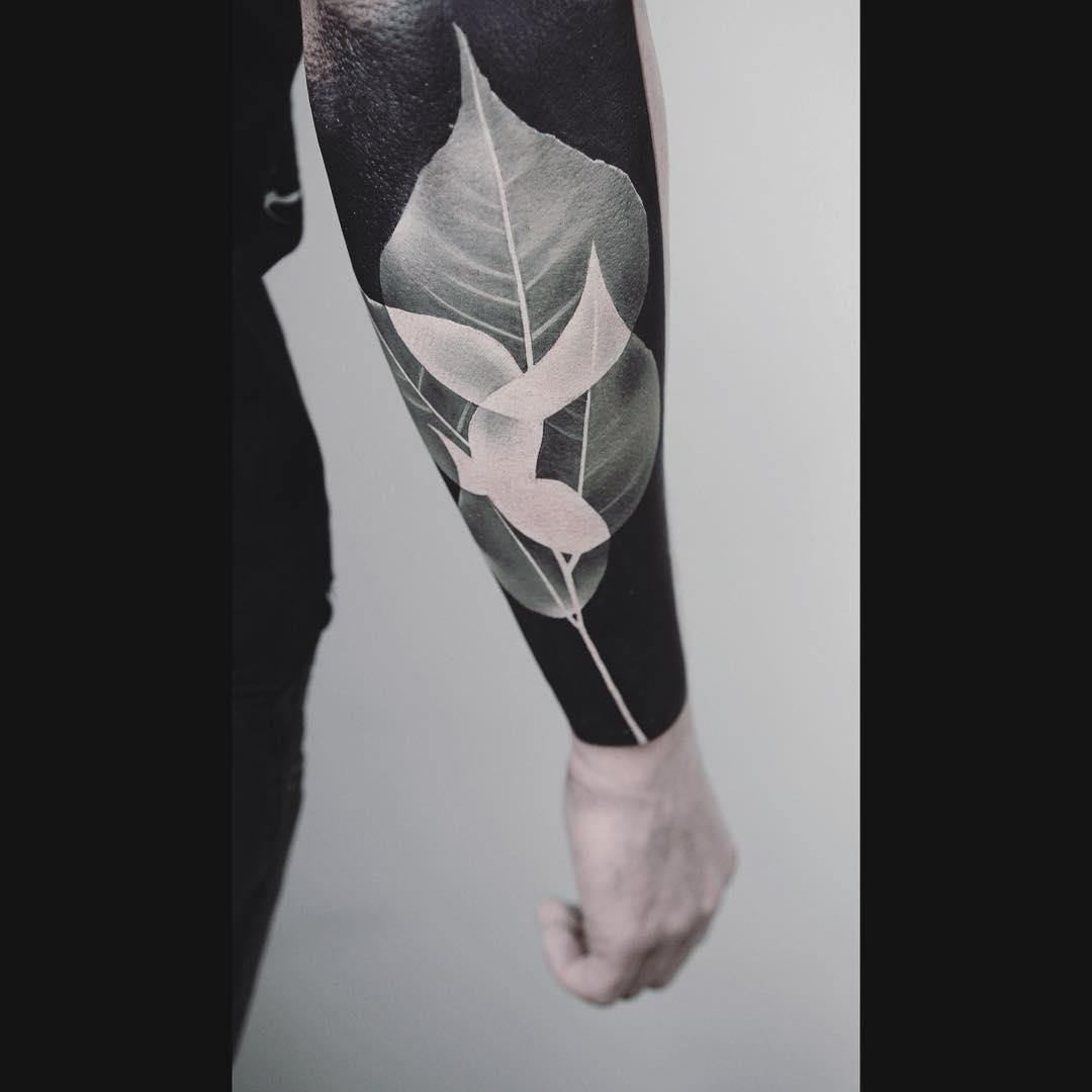Negative space leaf tattoo