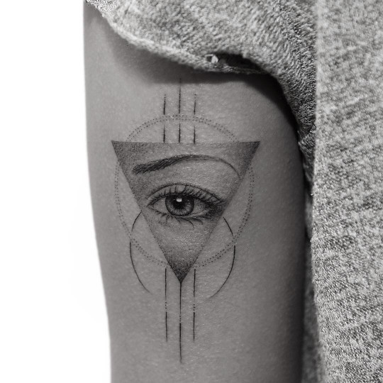 Realistic eye with an eyebrow tattoo in a triangle