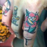 Rose stabbed finger tattoo