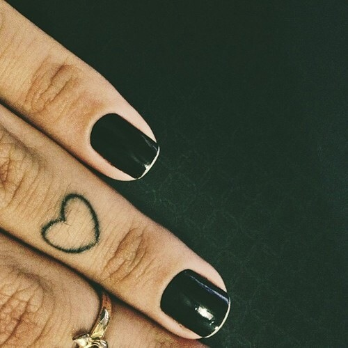Small black heart tattoo on the ring finger
