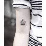 Small crown tattoo on the arm