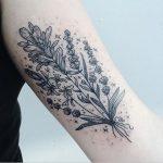 Subtle black wildflower tattoo