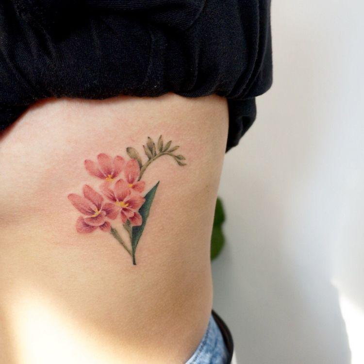 Subtle pink flower tattoo