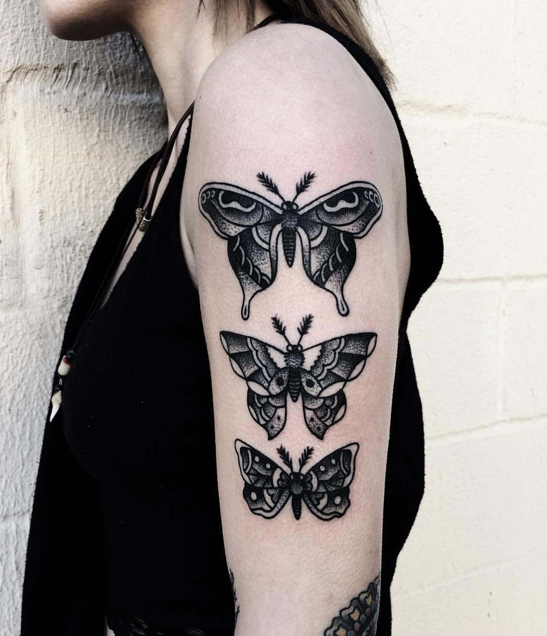 Three black butterflies on the left arm