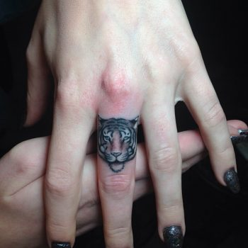 Tiger head tattoo on the middle finger