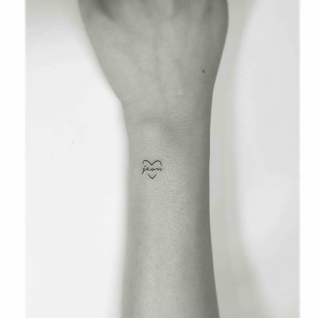 Tiny heart tattoo with a word