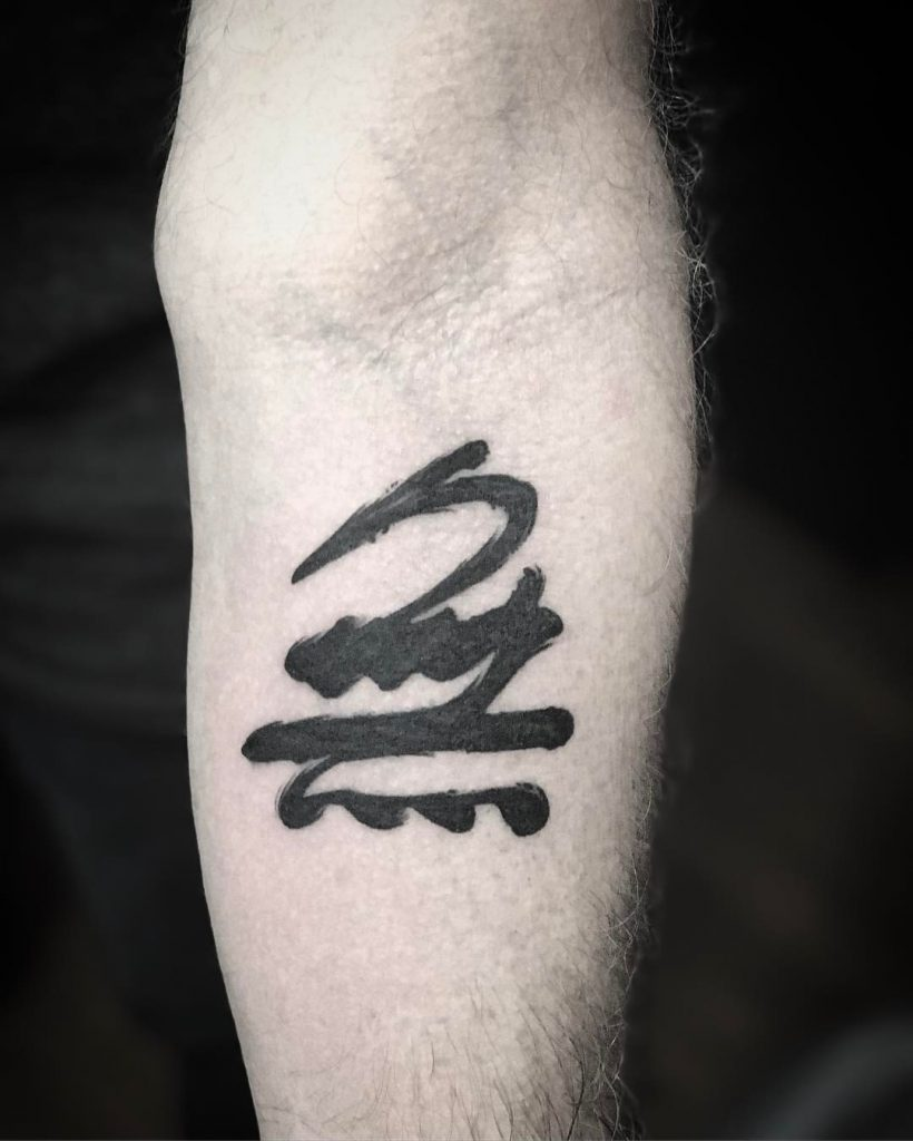 Abstract black tattoo on the forearm