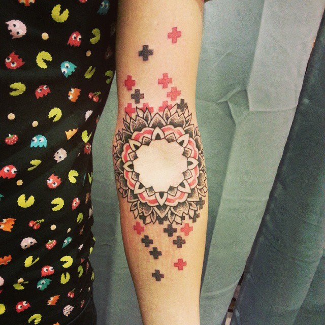 Black and red mandala tattoo with plus signs