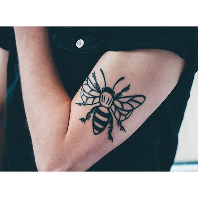 Black bee tattoo on the bicep