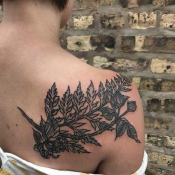 Black branch tattoo on the shoulder blade