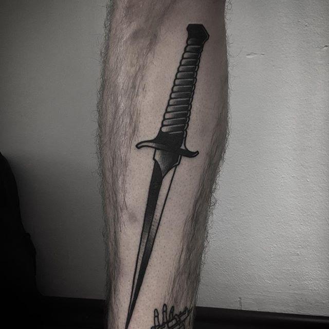 Black dagger tattoo on the calf