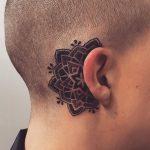 Black mandala tattoo behind the ear