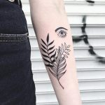 Black palm tree leaves and eye tattoo