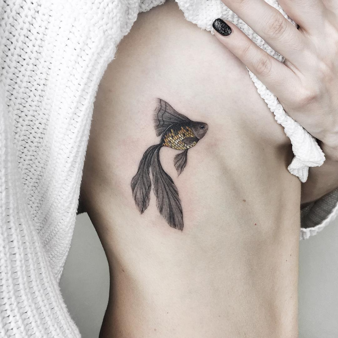 Black realistic fish tattoo on the rib cage