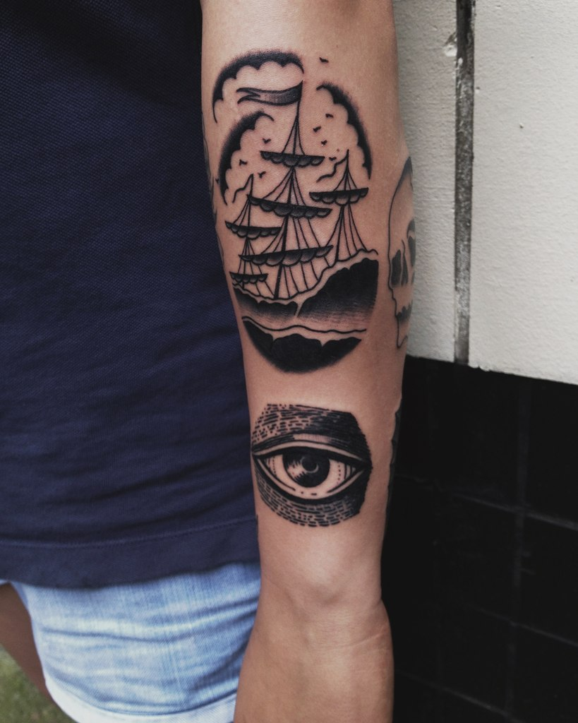 Black ship and eye tattoo on the arm