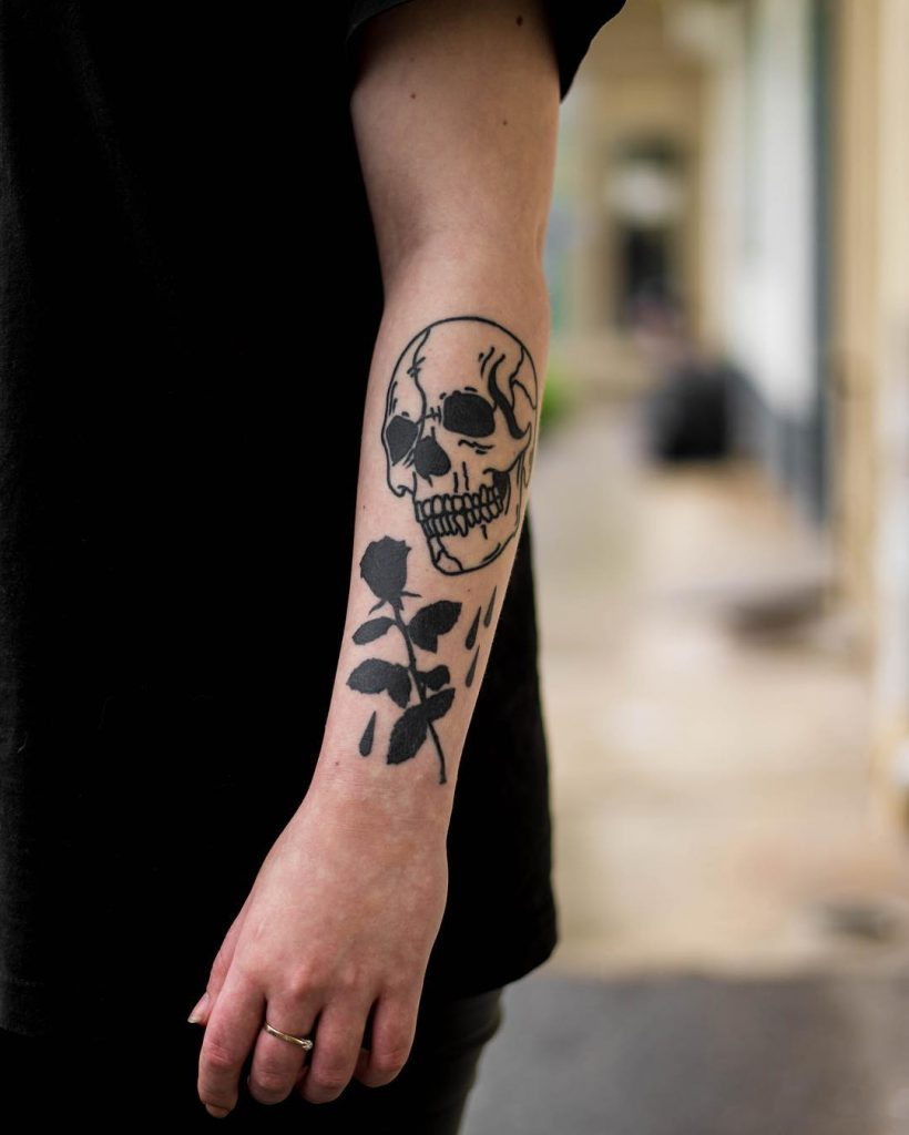 Black skull and rose tattoo on the forearm