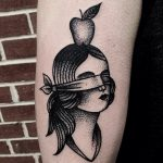 Blindfolded girl with an apple tattoo
