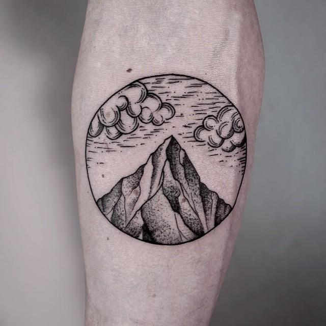 Circular mountain and clouds tattoo