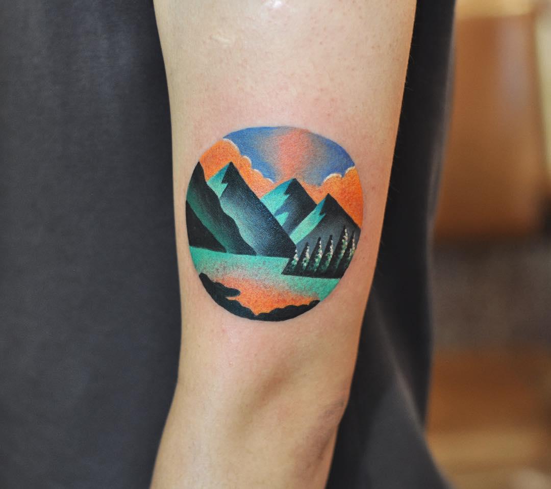 Circular mountainous landscape tattoo