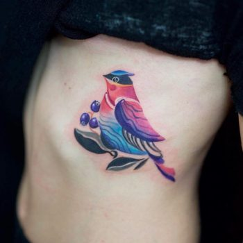 Colorful bird tattoo on the rib cage