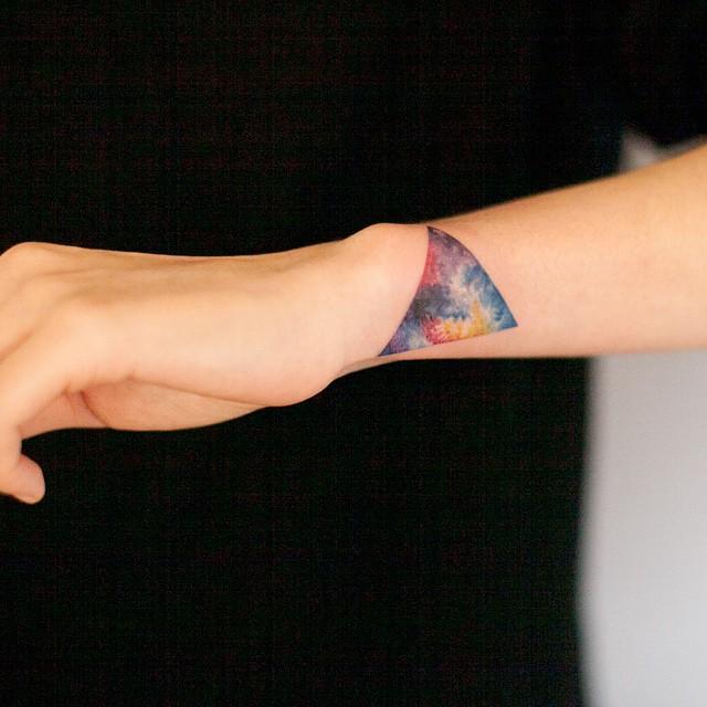 Colorful cosmic triangle tattoo