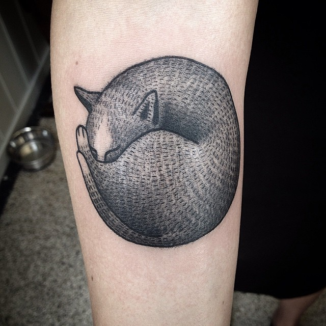 Curled up black fox tattoo