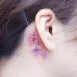 Delicate flower behind the ear tattoo