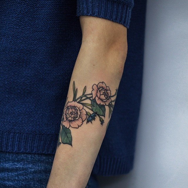 Delicate rose tattoo on the forearm