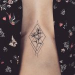 Flower in a rhombus tattoo on the sternum