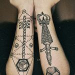 Key and dagger tattoos on forearms