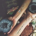 Matching arrow tattoos on inner forearms
