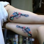 Matching floral gun tattoos