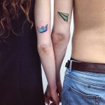 Matching paper plane and boat tattoo