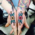 Matching traditional flower tattoos on hands