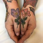 Matching violet and red flower tattoos on thumbs