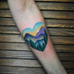 Mountainous landscape in a heart tattoo