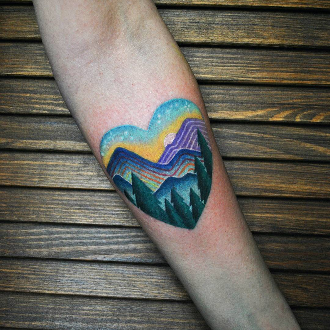 Mountainous landscape in a heart tattoo