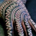 Negative space black pattern hand tattoo