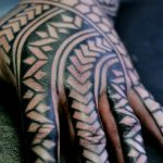Negative space black pattern hand tattoo