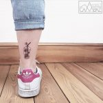Plastic cup with flowers tattoo on the ankle
