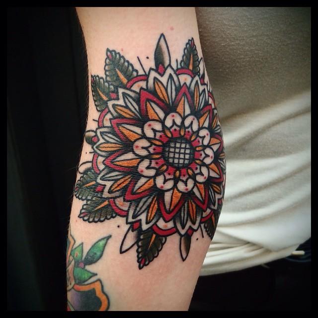 Red and orange mandala tattoo on the elbow