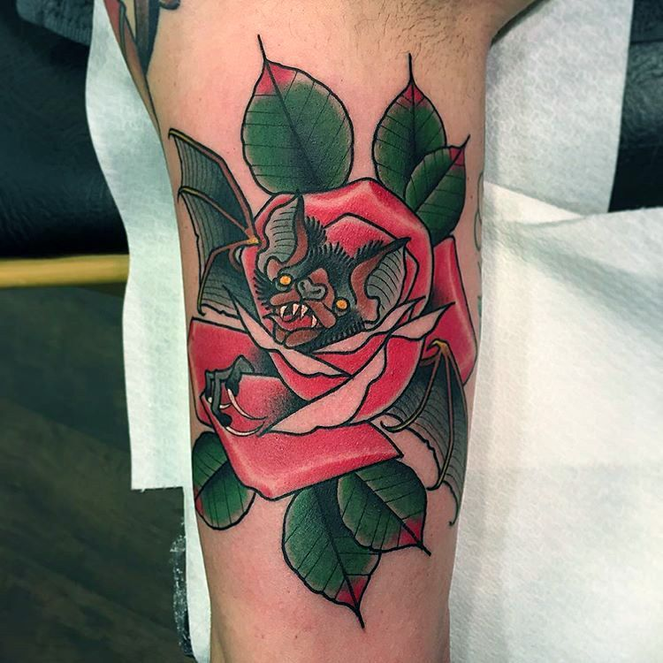 Red rose with green leaves tattoo